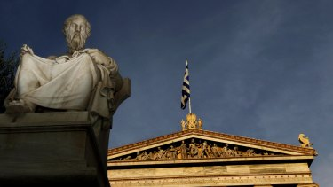 In this photo taken Friday, Oct. 21, 2011, a marble statues of ancient Greek philosopher Plato is seen on a plinth in front of the Athens Academy, as the Greek flag flies. More than 200 international philosophers braved strikes and protests to come to Greece this month to join a forum and debate matters of the mind. Greece's illustrious ancient thinkers built the foundations of Western scholarship, and their philosophy stands as an unquantifiable source of national wealth even during a financial crisis. (AP Photo/Petros Giannakouris)