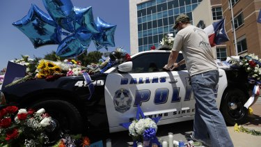 Michael O'Mahoney, a former police officer, places his patch on a make-shift memorial at the Dallas police headquarters.