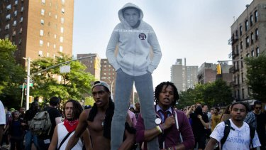 Demonstrators march through the Lower East Side neighborhood of Manhattan in New York holding a cut-out of Trayvon Martin during a protest against the acquittal of neighborhood watch member George Zimmerman.