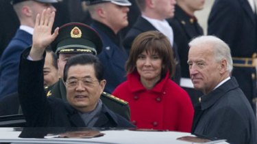 Warm welcome ... President Hu Jintao waves to well-wishers at Andrews Air Force Base, where he was greeted by the US Vice-President, Joe Biden, right.