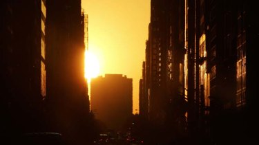 The sun sets  over the west side of New York City, known as Manhattanhenge