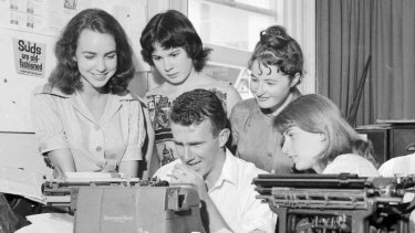 Madeleine St John (second right) peers over Clive James' shoulder at the University of Sydney in 1960.