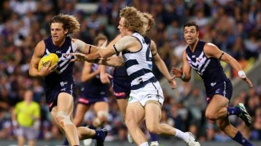 Nathan Fyfe avoids an attempted tackle by Geelong's Cameron Guthrie.