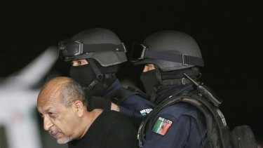 """Mexico's most-wanted drug lord Servando """"La Tuta"""" Gomez is escorted by police officers during a media conference about his arrest in Mexico City in February."""