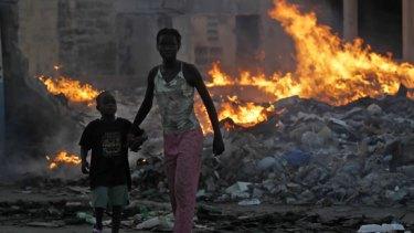 Survivors of Haiti's earthquake walk along a dump near the centre of Port-au-Prince.