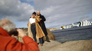 Tourists pose in front of the stricken Costa Concordia.