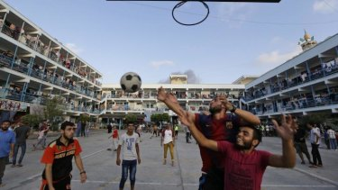 Displaced Palestinians play basketball in the courtyard of a UN school at Jebaliya refugee camp, in the northern Gaza Strip. The UN said rockets had been found at another such site.