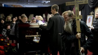 A man carries a cross as he walks by the coffin of regional parliament member Vyacheslav Markin, in Odessa, Ukraine.