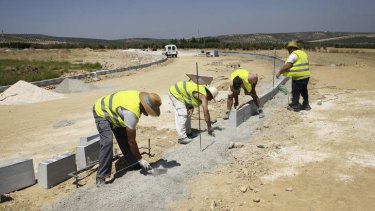A group of municipal job-lottery winners work on the construction of an industrial park in Alameda, Spain.