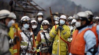 Civil defence teams search for survivors in Otsuchi, Japan.