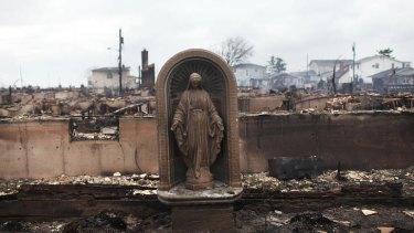 A Virgin Mary is all that remains from a home which was destroyed during superstorm Sandy in the Breezy Point neighbourhood.