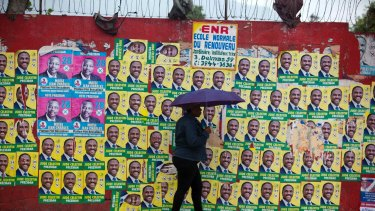 A woman walks with an umbrella as protection from a light rain, backdropped by a wall blanketed with presidential campaign posters, in Port-au-Prince, Haiti.