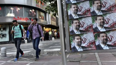Two Iranian men walk past posters of presidential candidate Mohsen Rezaei, a former Revolutionary Guard commander, a day prior to the election, in Tehran, Iran, Thursday, June 13, 2013.