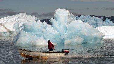 A fisherman sails past melting icebergs in Narsaq, Greenland.
