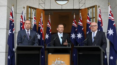 Ten-flag event:  Peter Dutton, Tony Abbott and George Brandis at a press conference at Parliament House on Tuesday.