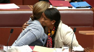 Senator Kate Lundy embraces Senator Nova Peris after she delivered a statement to the Senate on Thursday.