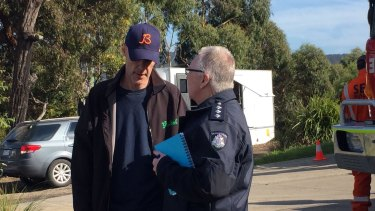 David Curry speaks to a police officer at Aireys Inlet, where his wife Elisa went missing.