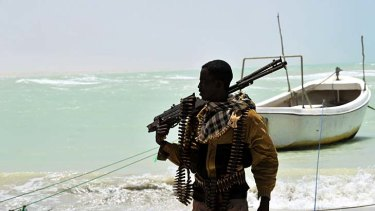 Part pirate, part armed militia, a Somali carries his high-calibre weapon along a beach in the central Somali town of Hobyo, a former Italian port.