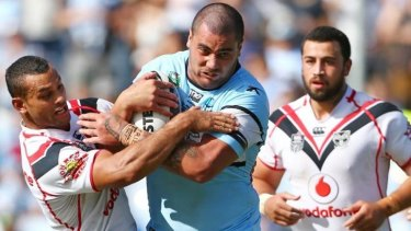 Ball and all: Cronulla's Andrew Fifita is wrapped up by the Warriors' Jayson Bukuya.