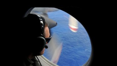 A crew member of a Royal New Zealand Airforce help to look for objects from the missing Malaysia Airlines flight MH370 flight.