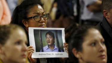 A supporter of Andrew Chan holds a picture of him at a vigil in Sydney on Tuesday.