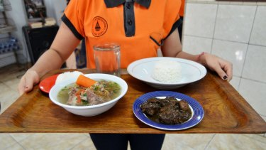 "A waiter serves soup and ""Sangsang"", a traditional cuisine of North Sumatra in Indonesia, which is made from the meat and blood of dog with chilli, in East Jakarta, Indonesia, in 2015."