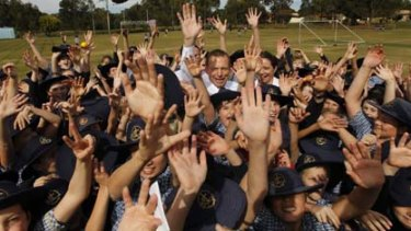 Opposition Leader Tony Abbott on the school oval with students during a visit to the Faith Lutheran College in Redlands in the south-east Queensland seat of Bowman today.