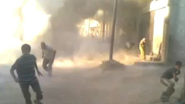 This still from an amateur video by Syrian activists shows people running for their lives during weekend attacks in Houla. More than 100 were killed, many of them children.