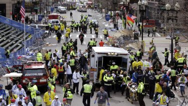 Medical workers aid injured people following the explosion at the finish line of the 2013 Boston Marathon in Boston.