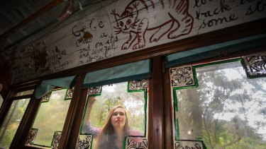 Karina Castan peers through the windows of Mirka Mora's art tram.