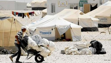 A Syrian refugee receives aid and rations at Al-Zaatri refugee camp in the Jordanian city of Mafraq.
