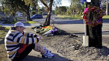 In mourning ... Lisa sits quietly at the crash site where her friend Kimberley Conna died in an accident on Monday.