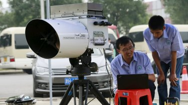 Engineers of Tianjin environmental monitoring centre use a device to check the level of hydrogen cyanide present in the air at a monitoring station within a three-kilometre exclusion zone around last week's explosion site.