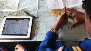 A Malaysian Maritime Enforcement Agency pilot studies a map onboard a Japanese aircraft.