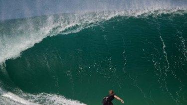 A surfer rides a large wave at Tamarama.