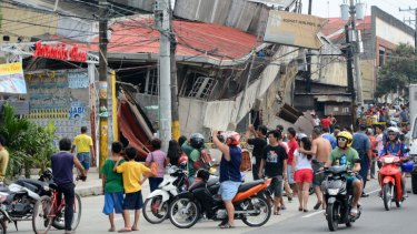 People gather next to damaged buildings in Cebu City.