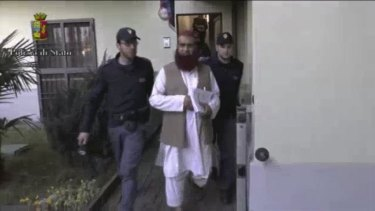 Italian Policemen detain a man suspected to be member of an armed organisation inspired by al-Qaeda in this still image taken from a video released by Italian Police.