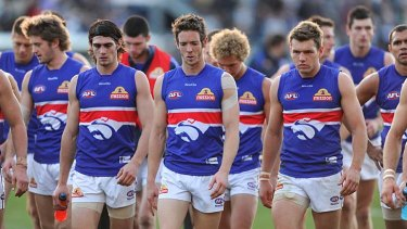 Sick puppies: The Western Bulldogs sulk from Skilled Stadium after their 61-point loss to Geelong yesterday.