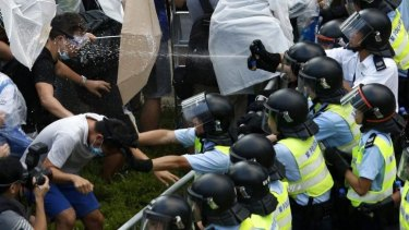 On attack: Riot police use pepper spray as tens of thousands of protesters block the main street to the financial district outside the government headquarters in Hong Kong.