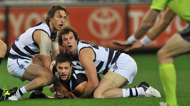 Caught: Collingwood's Nathan Brown is wrapped up by Geelong players at the soaked MCG yesterday.