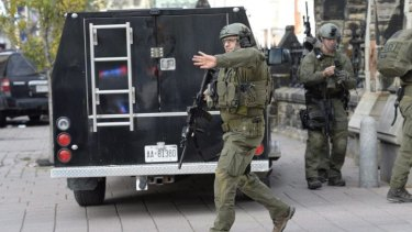 A Mounted Police intervention team clears the area at the entrance of Parliament in Ottawa following the attack.