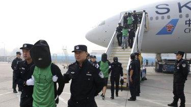 In this photo released by Xinhua News Agency, Chinese suspects involved in wire fraud are escorted off a plane upon arriving at the Beijing Capital International Airport on Wednesday.