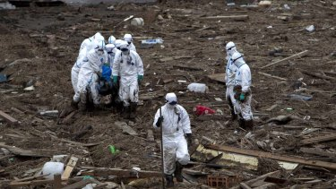 Grim Task ... Japanese police, wearing protective clothing, carry a body recovered from the rubble in a rise paddy in the Fukushima Prefecture.