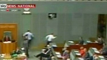 Television cameras show Opposition Leader Tony Abbott running for the exit at Parliament House yesterday.