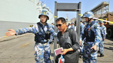 Chinese navy soldiers of the People's Liberation Army (PLA) gesture to Chinese citizens boarding the naval ship Linyi at a port in Aden during their evacuation.
