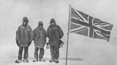 Irish explorer Sir Ernest Henry Shackleton and two members of his expedition team beside a Union Jack within 111 miles of the South Pole, a record feat. Circa 1909.