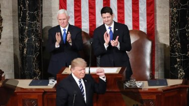 President Donald Trump, flanked by Vice President Mike Pence and House Speaker Paul Ryan, gestures on Capitol Hill in Washington, on Tuesday.