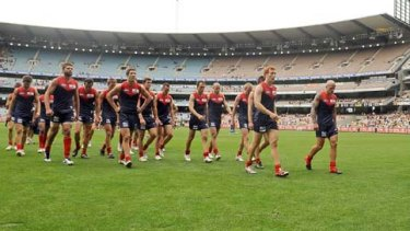 A dejected Melbourne outfits leaves the ground after being hammered by Hawthorn.