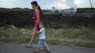 Frightful sight: A woman and child walk past the crash site.