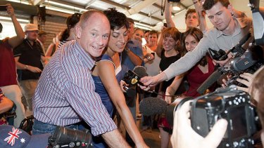 Campbell Newman and wife Lisa fight their way through the media crush to cast their votes in the seat of Ashgrove.